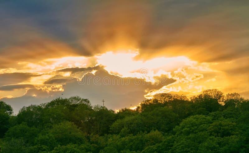 Ηλιοβασίλεμα πέρα από την εκκλησία στο πάρκο το καλοκαίρι στοκ φωτογραφία
