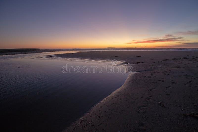 Ηλιοβασίλεμα πέρα από την παλιρροιακή εκροή ποταμών της Σάντα Κλάρα στο Ειρηνικό Ωκεανό στο κρατικό πάρκο McGrath στην ακτή Καλιφ στοκ εικόνα