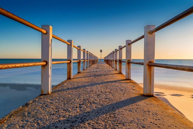 Ηλιοβασίλεμα πέρα από την ωκεάνιου και συγκεκριμένου αποβάθρα παραλιών, ή λιμενοβραχίονας στοκ φωτογραφία με δικαίωμα ελεύθερης χρήσης