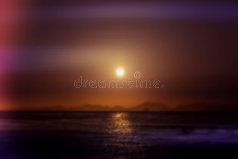 Θολωμένο περίληψη υπόβαθρο Ηλιοβασίλεμα πέρα από τη γραμμή θάλασσας και βουνών στους ρόδινους τόνους Πορεία ήλιων στο νερό στοκ εικόνα