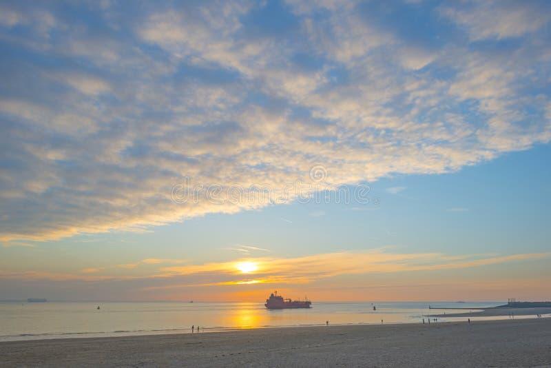 Ηλιοβασίλεμα πέρα από τη θάλασσα κατά μήκος μιας παραλίας κάτω από έναν μπλε νεφελώδη ουρανό στην πτώση στοκ εικόνες
