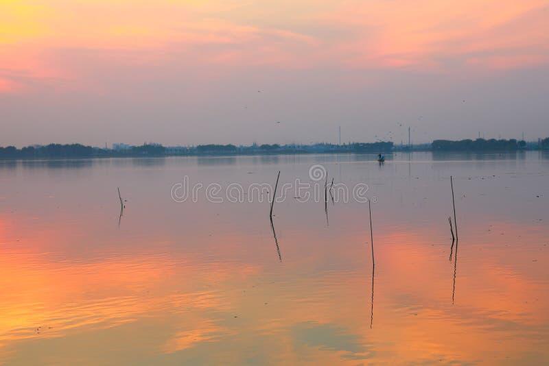 Ηλιοβασίλεμα πέρα από τη λίμνη, σειρές ατόμων ένα αλιευτικό σκάφος στοκ φωτογραφία με δικαίωμα ελεύθερης χρήσης