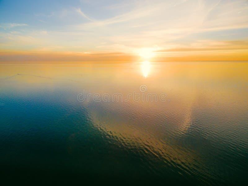 Ηλιοβασίλεμα πέρα από το ήρεμο ωκεάνιο νερό στοκ εικόνες