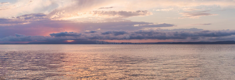 Ηλιοβασίλεμα παραδείσου πυράκτωσης πέρα από το νερό Πορφυρό ηλιοβασίλεμα πέρα από τη θάλασσα στοκ εικόνα