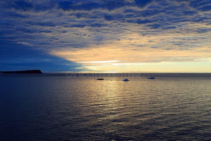 Ηλιοβασίλεμα που κρύβεται από τα πυκνά σύννεφα και που απεικονίζεται στο νερό στοκ φωτογραφίες