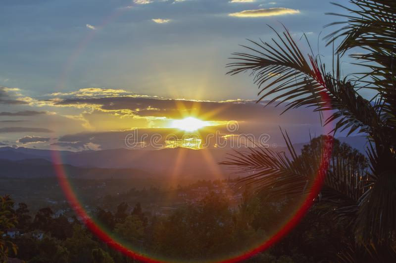 Ηλιοβασίλεμα που πλαισιώνεται με τα φύλλα φοινικών και μια κόκκινη φλόγα φακών στοκ φωτογραφία με δικαίωμα ελεύθερης χρήσης