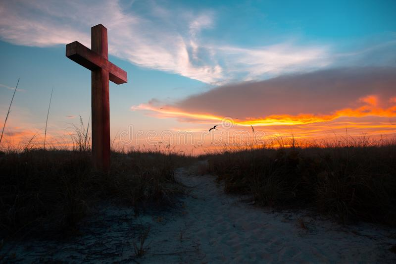 Ηλιοβασίλεμα που φωτίζει έναν σταυρό στοκ εικόνες
