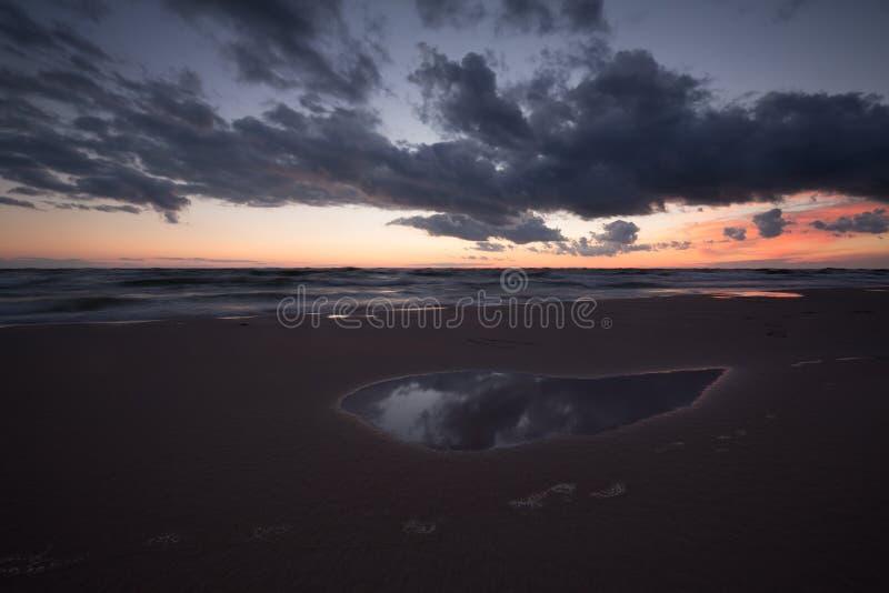 Ηλιοβασίλεμα στην παραλία με τα σύννεφα που απεικονίζουν σε μια ομάδα του νερού στοκ εικόνα με δικαίωμα ελεύθερης χρήσης