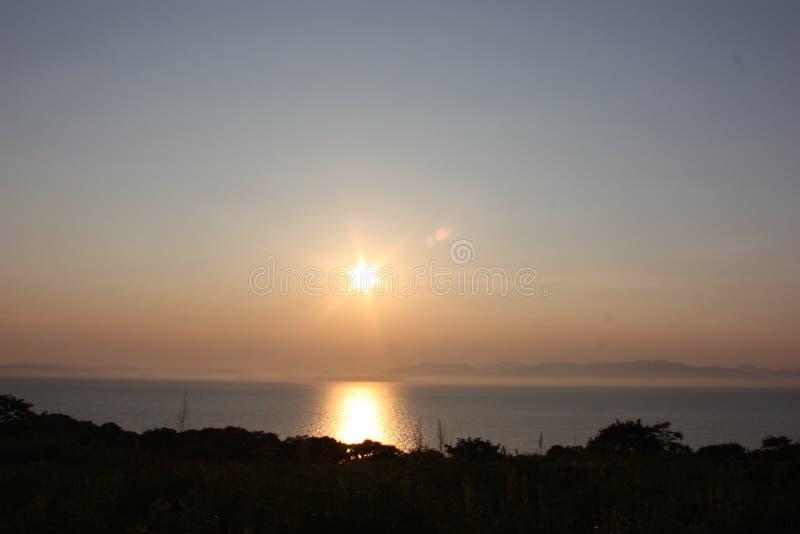 Ηλιοβασίλεμα στην παραλία πέρα από το δάσος στοκ εικόνες