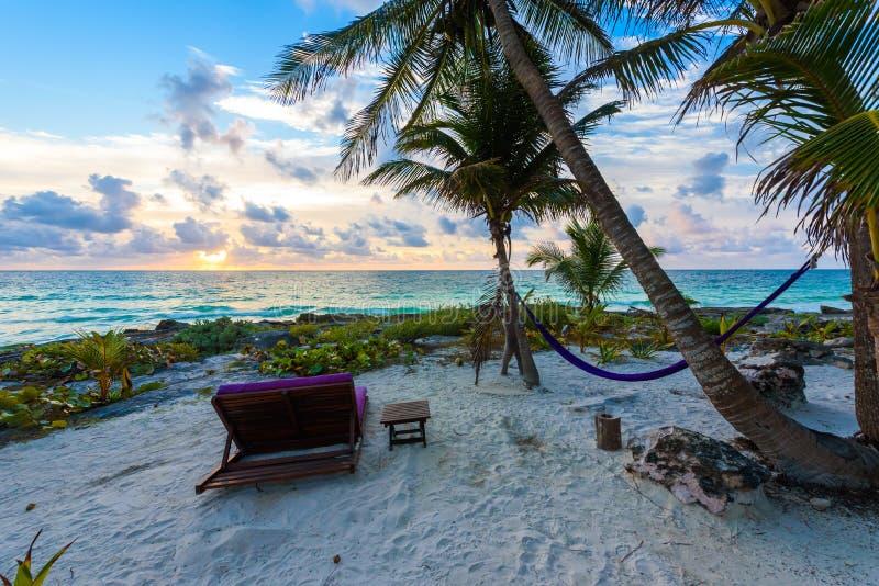 Ηλιοβασίλεμα στην παραλία παραδείσου - έδρες κάτω από τους φοίνικες στην παραλία στο τροπικό θέρετρο Riviera Maya - καραϊβική ακτ στοκ εικόνες με δικαίωμα ελεύθερης χρήσης