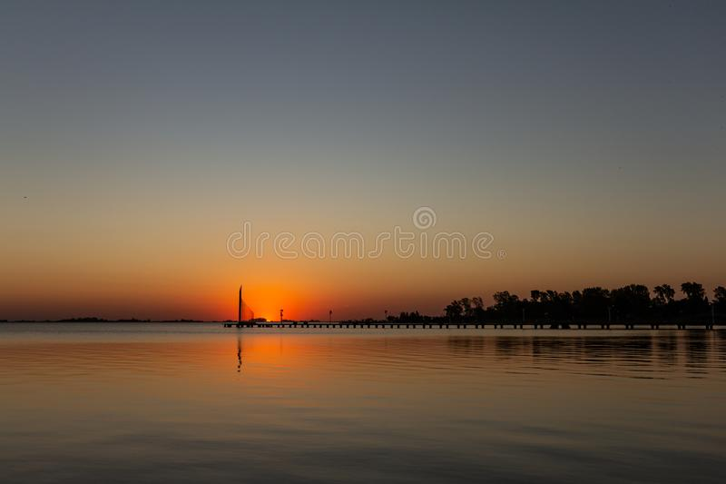 Ηλιοβασίλεμα στη λίμνη Ο ήλιος απεικονίζει το φως του στη λίμνη στοκ εικόνα