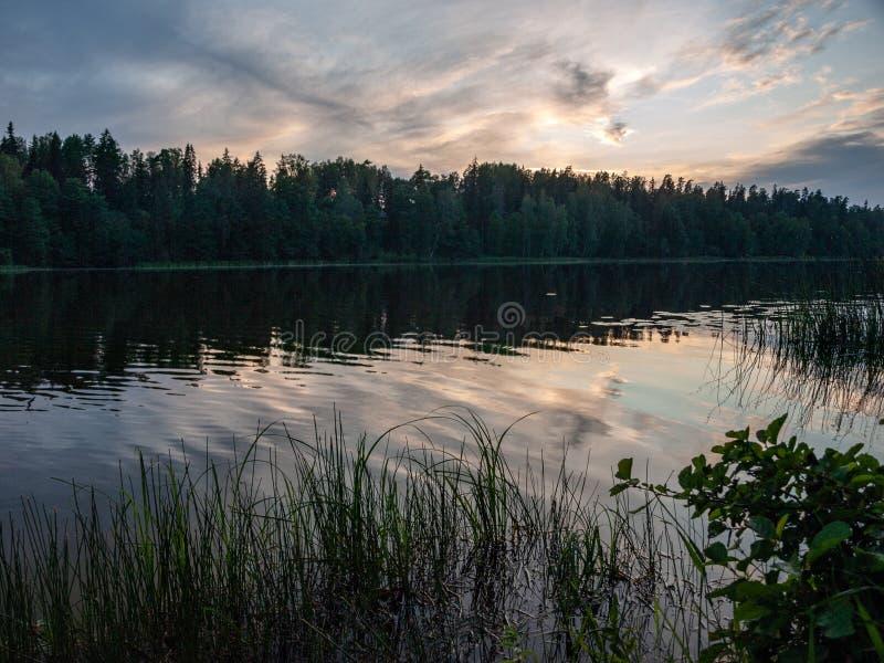 Ηλιοβασίλεμα στη λίμνη όμορφα χρώματα χαοτικά σύννεφα στοκ εικόνα
