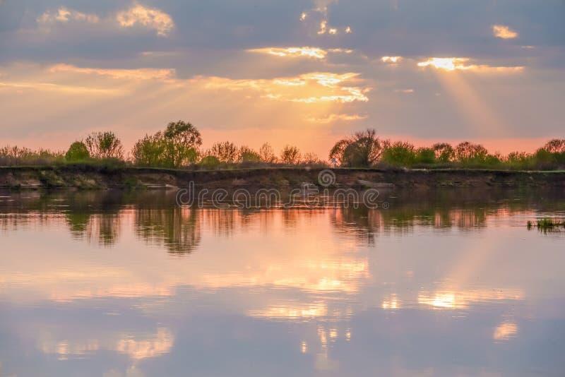 Ηλιοβασίλεμα στη λίμνη όμορφο ηλιοβασίλεμα πίσω από τα σύννεφα επάνω από το υπόβαθρο τοπίων λιμνών πλεονάσματος o στοκ εικόνα