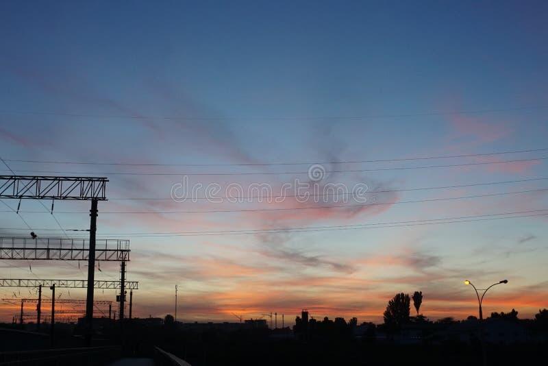 Ηλιοβασίλεμα στη στάση τραίνων με τον όμορφο βαθύ μπλε ουρανό και τα κόκκινα σύννεφα στοκ εικόνες