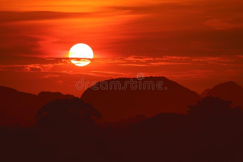 ηλιοβασίλεμα στον κόκκινο ουρανό νύχτας πίσω πέρα από το βουνό δέντρων σκιαγραφιών στοκ φωτογραφία με δικαίωμα ελεύθερης χρήσης