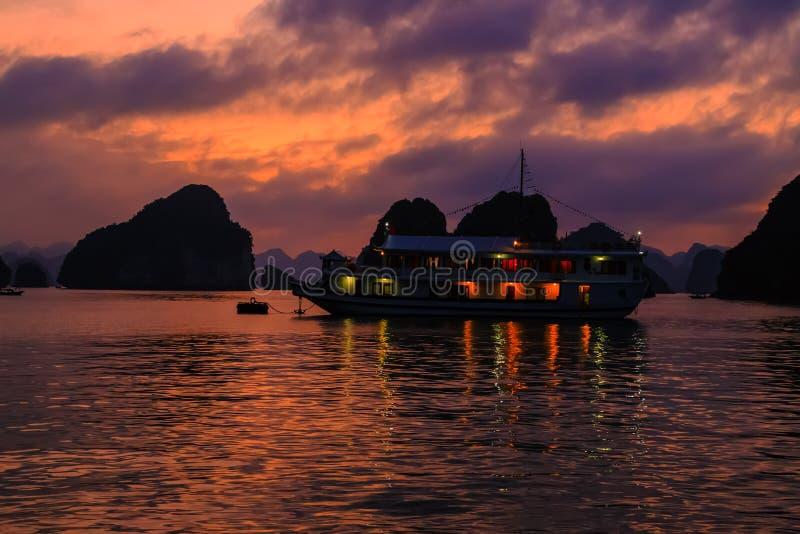 ηλιοβασίλεμα στον κόλπο Halong Ξύλινα παλιοπράγματα σκαφών κρουαζιέρας παραδοσιακά που πλέουν το μακρύ κόλπο εκταρίου, περιοχή πα στοκ φωτογραφίες