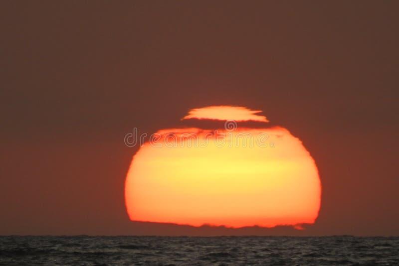 Ηλιοβασίλεμα στον ορίζοντα πέρα από τη θάλασσα στοκ εικόνα