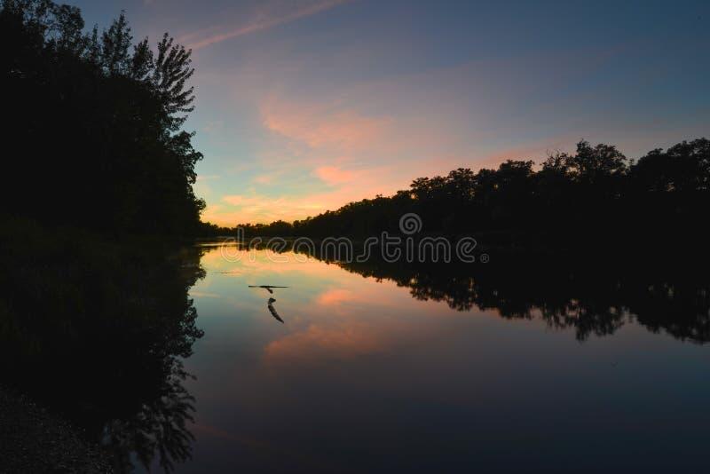 Ηλιοβασίλεμα στον ποταμό του ST Croix μεταξύ Μινεσότας και του Ουισκόνσιν - δέντρα απεικόνισε στα ήρεμα νερά - μπλε, το πορτοκαλί στοκ εικόνες με δικαίωμα ελεύθερης χρήσης