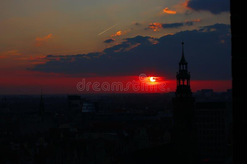 Ηλιοβασίλεμα στο ιστορικό κέντρο της πόλης τα σύνολα ήλιων πέρα από τον ορίζοντα στο φωτεινό φως και τα σύννεφα κώνοι των σπιτιών στοκ φωτογραφίες με δικαίωμα ελεύθερης χρήσης