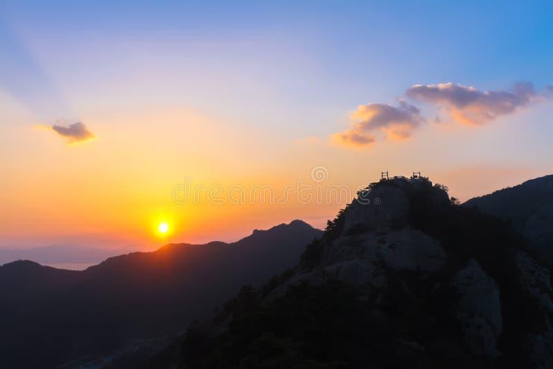 Ηλιοβασίλεμα το βράδυ, νεφελώδες με τα βουνά και το όμορφο κόκκινο ο στοκ φωτογραφία