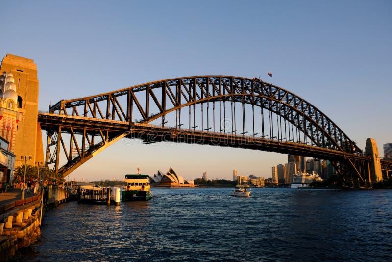 Ηλιοβασίλεμα, Όπερα του Σίδνεϊ, γέφυρα και πορθμείο, Αυστραλία στοκ φωτογραφία