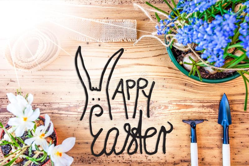 Ηλιόλουστα λουλούδια ανοίξεων, καλλιγραφία ευτυχές Πάσχα, ξύλινο υπόβαθρο στοκ φωτογραφία με δικαίωμα ελεύθερης χρήσης