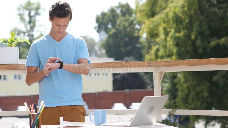 Ηλιόλουστη ημέρα, άτομο που στέκεται και που χρησιμοποιεί Smartwatch στο μπαλκόνι, συσκευή στοκ εικόνα