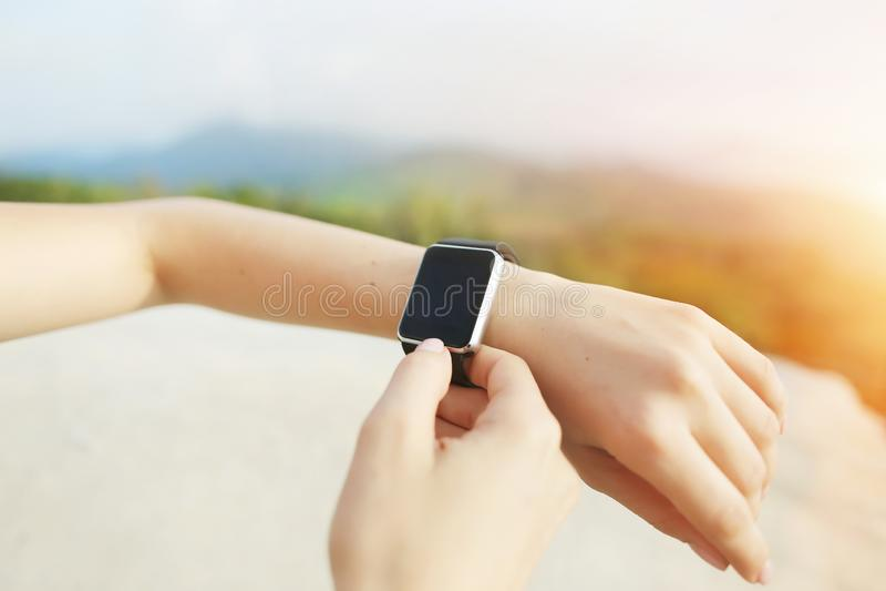 Ηλιόλουστη φωτογραφία των χεριών κινηματογραφήσεων σε πρώτο πλάνο που χρησιμοποιούν smartwatch με τα βουνά στο υπόβαθρο στοκ φωτογραφίες