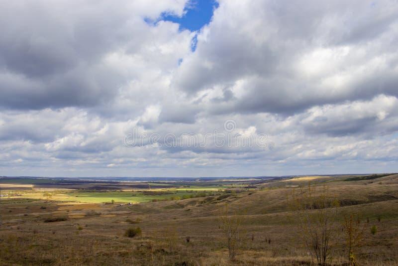 Ηλιόλουστοι κίτρινοι τομείς τοπίων άνοιξη με τα μαύρα εξασθενισμένα σημεία, μπλε νεφελώδεις τομείς ουρανού Αγροτικό τοπίο επαρχία στοκ φωτογραφία με δικαίωμα ελεύθερης χρήσης