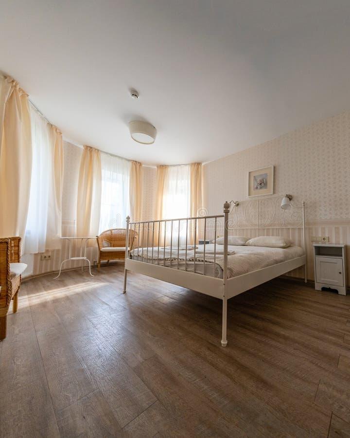Ηλιόλουστο εσωτερικό στο δωμάτιο ξενοδοχείων πολυτελείας με τη βασίλισσα Sized Bed, Comcept των άνετων ακριβών ταξιδιών στοκ φωτογραφίες