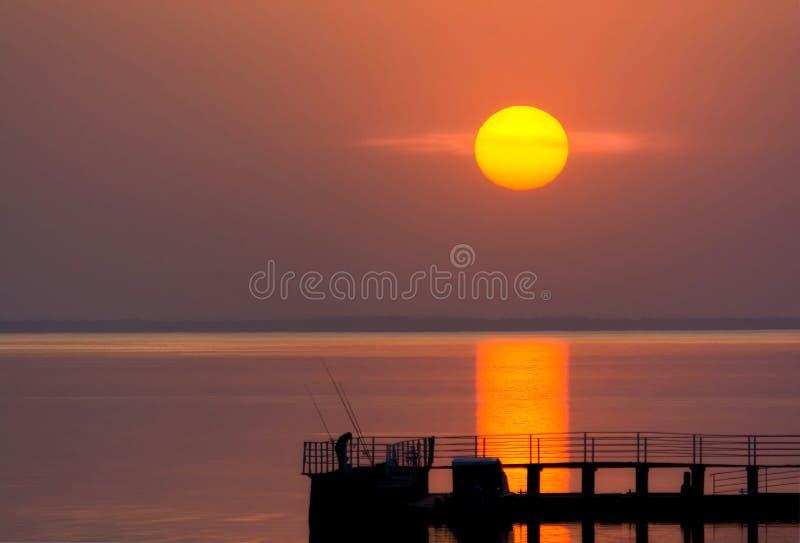 Ηλιόλουστο ηλιοβασίλεμα πέρα από το νερό Σκιαγραφία ενός ψαρά όμορφη φύση στοκ εικόνα
