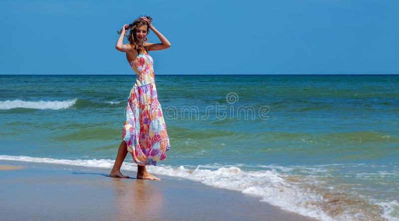 Ηλιόλουστο θερινό πορτρέτο του ευτυχούς όμορφου νέου κοριτσιού brunette που έχει τη διασκέδαση στην παραλία της μπλε θάλασσας ταξ στοκ εικόνες με δικαίωμα ελεύθερης χρήσης