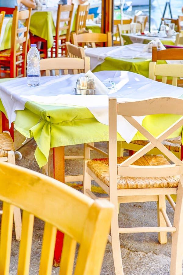 Ηλιόλουστο υπαίθριο εστιατόριο στην πόλη Chania στην Κρήτη Διακοσμημένα wirh ελληνικά πράσινα και κιτρινωπά χρώματα στοκ φωτογραφία με δικαίωμα ελεύθερης χρήσης