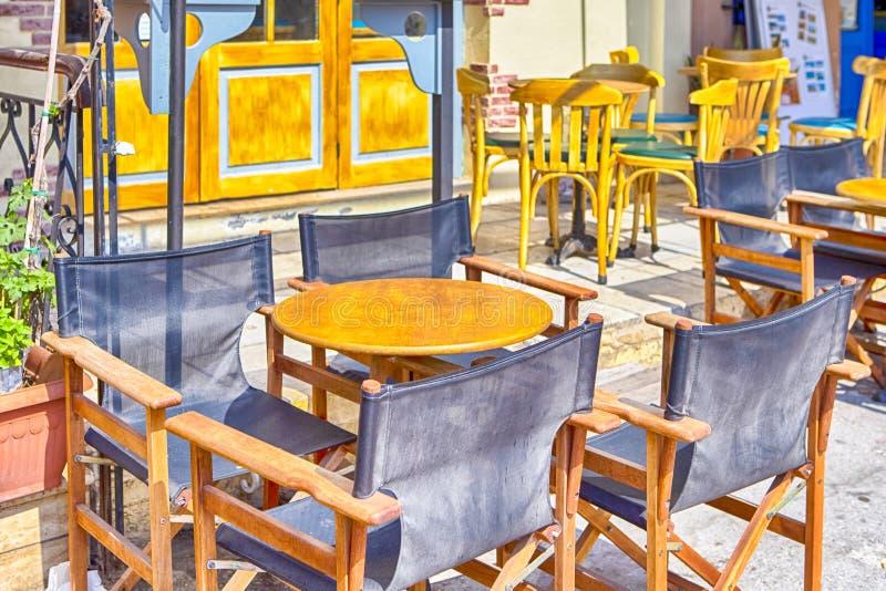 Ηλιόλουστο υπαίθριο εστιατόριο στην πόλη Chania στην Κρήτη Διακοσμημένος με τα ελληνικά πράσινα και κιτρινωπά χρώματα στοκ φωτογραφίες με δικαίωμα ελεύθερης χρήσης