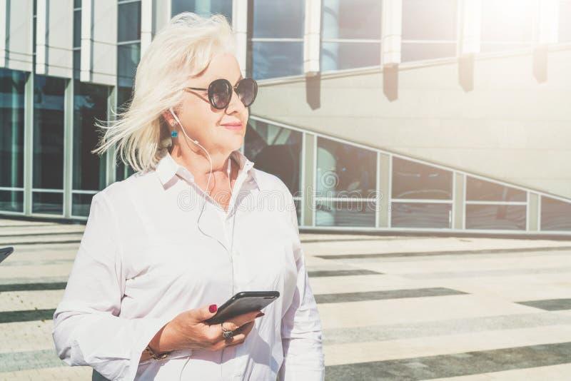 ημέρα ηλιόλουστη Η μέσης ηλικίας γυναίκα, η συνταξιούχος γυναίκα που ντύνονται στο άσπρο πουκάμισο και τα γυαλιά ηλίου, στάσεις σ στοκ φωτογραφία με δικαίωμα ελεύθερης χρήσης