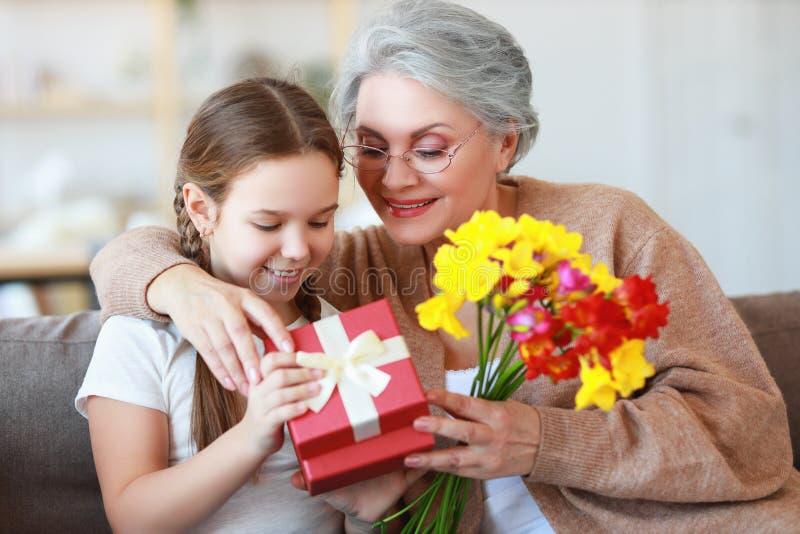 Ημέρα μητέρας και γιαγιάδων! η οικογενειακή εγγονή συγχαίρει τη γιαγιά της στις διακοπές και δίνει τα λουλούδια και τα δώρα στοκ φωτογραφίες