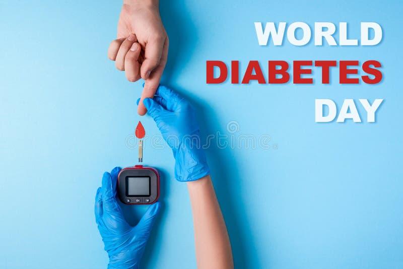 Ημέρα παγκόσμιου διαβήτη επιγραφής, νοσοκόμα που κάνει ένα χέρι ατόμων ` s εξετάσεων αίματος με το κόκκινο αίμα να μειωθεί και το στοκ φωτογραφία