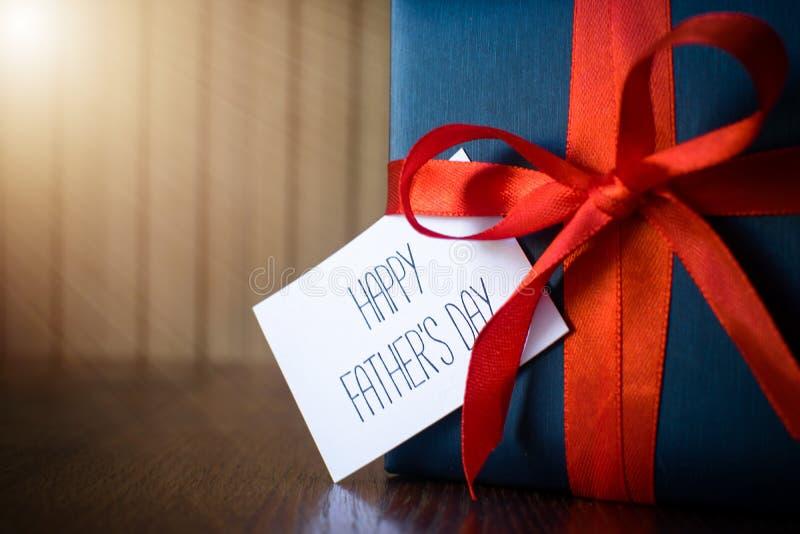 Ημέρα πατέρων Συσκευασία δώρων που τυλίγεται με το μπλε έγγραφο και το σχοινί με μια κόκκινη κορδέλλα στο ξύλινο υπόβαθρο στοκ φωτογραφία με δικαίωμα ελεύθερης χρήσης