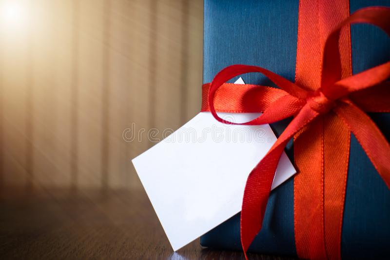 Ημέρα πατέρων Συσκευασία δώρων που τυλίγεται με το μπλε έγγραφο και το σχοινί με μια κόκκινη κορδέλλα στο ξύλινο υπόβαθρο Copyspa στοκ εικόνες