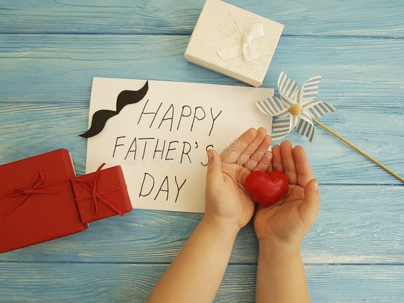 Ημέρα πατέρων ` s, χέρια μωρών ` s, κόκκινη καρδιά συγχαρητηρίων σχεδίου σε ένα μπλε ξύλινο υπόβαθρο στοκ εικόνα με δικαίωμα ελεύθερης χρήσης