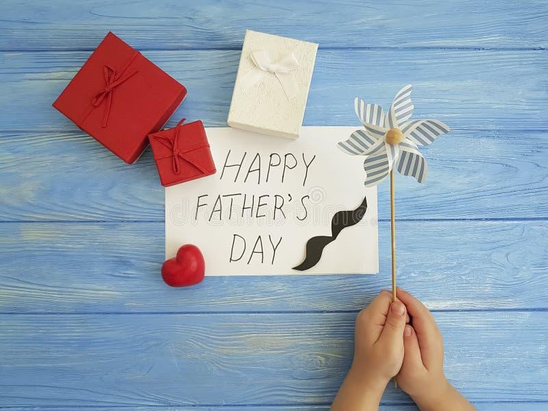 Ημέρα πατέρων ` s, χέρια μωρών ` s, κόκκινη καρδιά συμβόλων σε ένα μπλε ξύλινο υπόβαθρο στοκ φωτογραφία