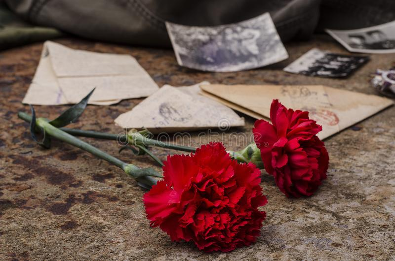 Ημέρα της Νίκης Γαρίφαλα σε φόντο σκουριασμένου σιδήρου με παλαιά στρατιωτικά γράμματα και φωτογραφίες Ο Μεγάλος Πατριωτικός Πόλε στοκ εικόνα