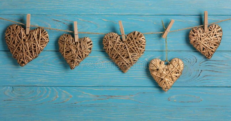 Ημέρα του ευτυχούς βαλεντίνου! Διακοσμητικές ψάθινες καρδιές του χρυσού χρώματος σε ένα μπλε ξύλινο υπόβαθρο στοκ φωτογραφίες