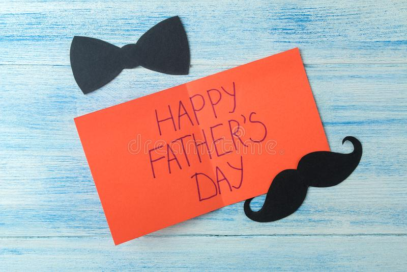 ημέρα του ευτυχούς πατέρα Κείμενο και διακοσμητικό αρσενικό mustache και δεσμός τόξων στο ανοικτό μπλε ξύλινο υπόβαθρο r στοκ εικόνα