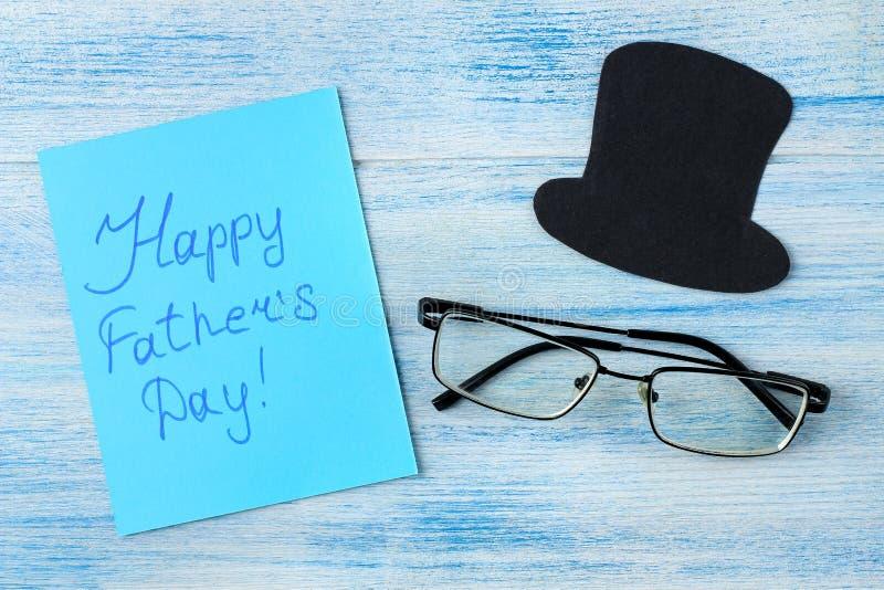 Ημέρα του ευτυχούς πατέρα κείμενο και καπέλο και γυαλιά των διακοσμητικών ατόμων σε ένα ανοικτό μπλε ξύλινο υπόβαθρο r στοκ εικόνες με δικαίωμα ελεύθερης χρήσης
