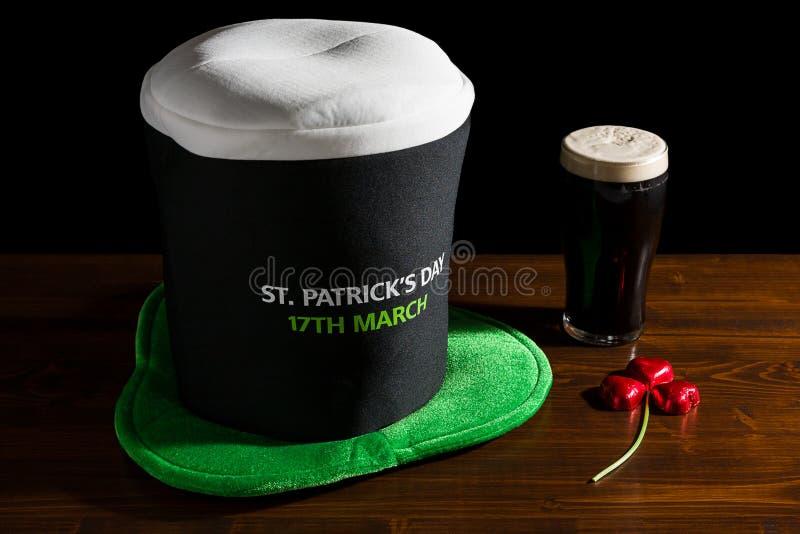 Ημέρα του ST Πάτρικ με μια πίντα της μαύρων μπύρας, του καπέλου και του τριφυλλιού στοκ φωτογραφία