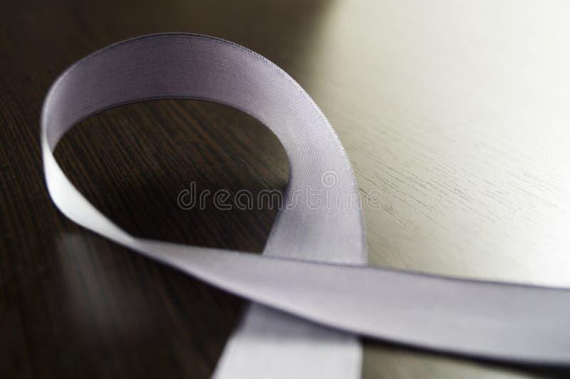 Ημέρα Parkinson Μια ασημένια κορδέλλα ως σύμβολο σε ένα σκοτεινό υπόβαθρο στοκ φωτογραφίες