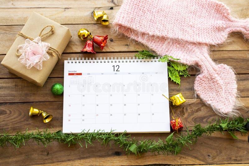 Ημερολόγιο Δεκέμβριος με κουτί δώρων για την ημέρα του φεστιβάλ και μαντίλα για πλέξιμο στοκ εικόνα