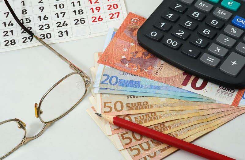 Ημερολόγιο, γυαλιά, κόκκινο μολύβι, ευρώ και υπολογιστής στοκ εικόνες