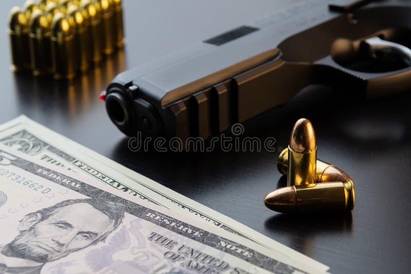 Ημιαυτόματα πιστόλι, σφαίρες και τραπεζογραμμάτια δολαρίων στο μαύρο υπόβαθρο στοκ εικόνα με δικαίωμα ελεύθερης χρήσης